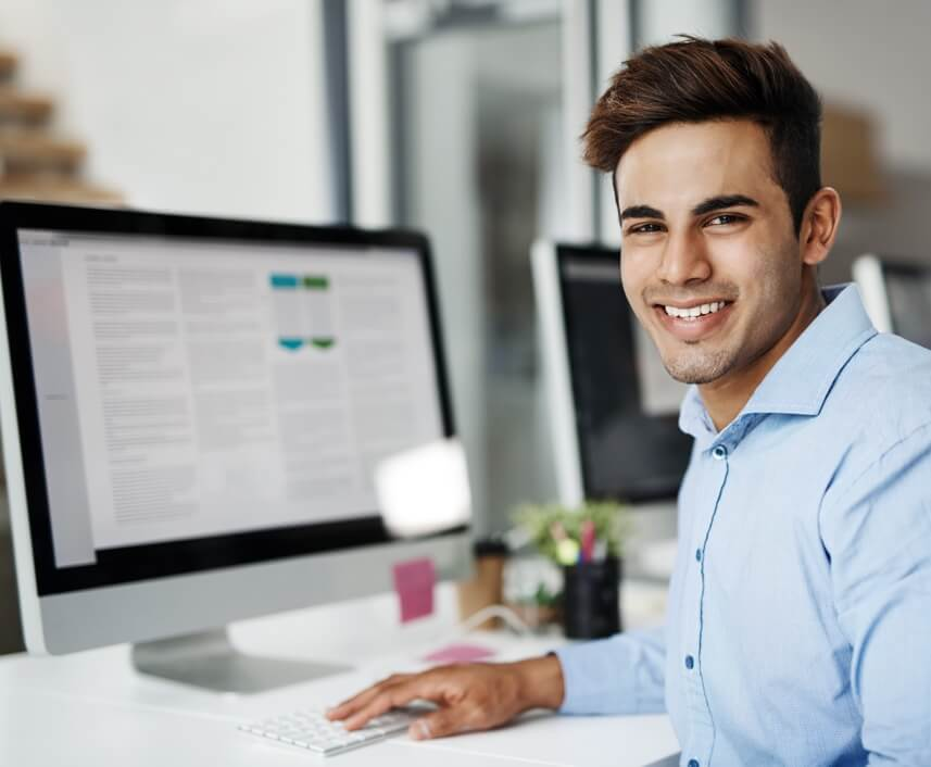 Photo of person smiling with a computer in the background